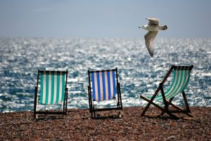 Three empty deck chairs on a beach with blue sky and the sea in the background