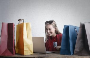 woman sits at table looking at laptop surrounded by bags of shopping