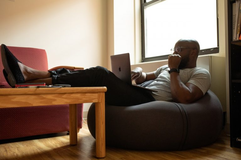 Man relaxed working from home on laptop, sat on bean bag with feet up on coffee table