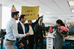 group of office workers smiling with happy birthday signs and party hats