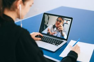 woman with earphones sat at desk video calling colleague