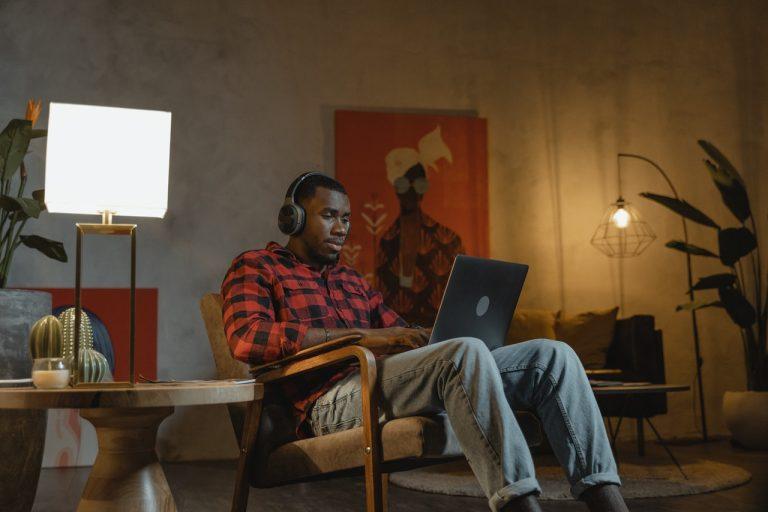 man-in-big-chair-working-on-laptop-headphones-on