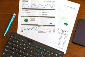 documents on a table showing charts, tables and web analytics. next to a keyboard and a pen