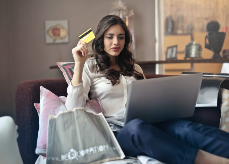 woman sitting in chair with laptop and holding a credit card