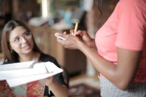 waitress making notes talking to smiling customer sat at table